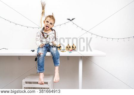 A Little Boy In A Zombie Costume Sits On A Table And Makes Grimaces.