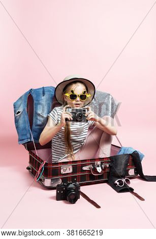 Travel: A Schoolgirl Girl Is Preparing For A Trip, Sitting In A Large Suitcase With Things And Holdi