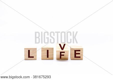 Spinning Wooden Dice By Changing The Word Life To Live. White Background