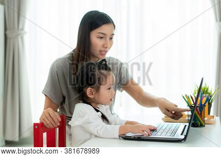 Asian Kindergarten School Girl  With Mother Video Conference E-learning With Teacher On Laptop In Li