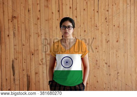 Woman Wearing India Flag Color Shirt And Standing With Two Hands In Pant Pockets On The Wooden Wall