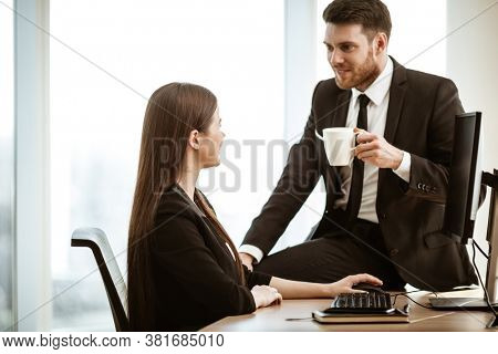 Flirt and relations at work. Happy smiling male businessman sits and shows sexual interest to positive minded female assistant at workplace. Two people man and woman love and sympathy in modern office