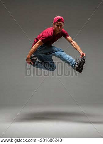 Cool Young Guy Breakdancer Jumps In Studio On Gray Background. Battle Competitions Announcement