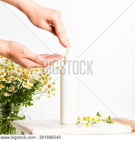 Woman Pushing Pump Plastic Lotion Or Soap Bottle With Copy Space