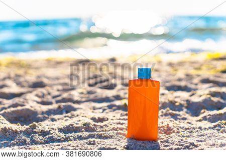 Protective Sunscreen Or Sunblock And Sunbathe Lotion In Orange Plastic Bottles On Tropical Beach. Su