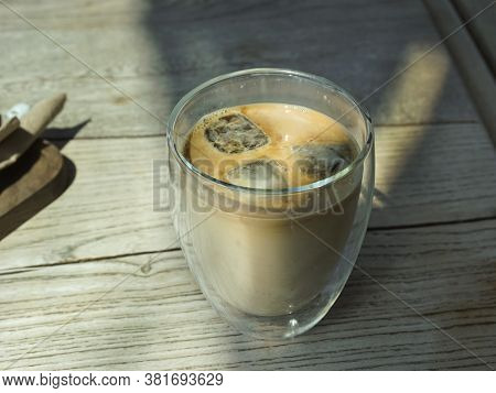 Ice Cubes Of Coffee Poured With Milk. Iced Coffee In A Glass On A Wooden Table. Coffee Cube Iced. Ic