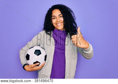 African american curly player woman playing soccer holding football bal over purple background happy with big smile doing ok sign, thumb up with fingers, excellent sign