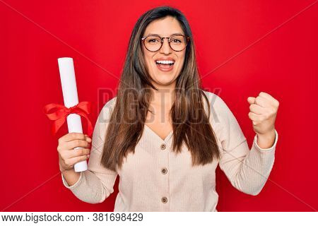 Young hispanic smart woman wearing glasses holding university degree over red background screaming proud and celebrating victory and success very excited, cheering emotion