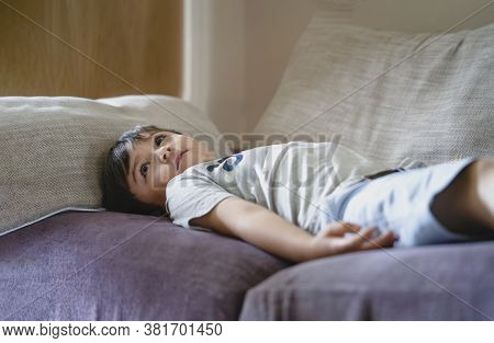 New Normal Lifestyle Happy Kid Lying On Sofa Watching Tv, Cute Child Laying On Comfy Couch And Looki