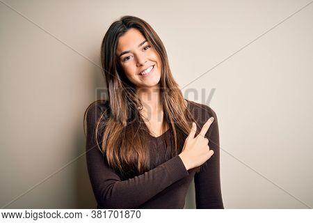 Young beautiful girl wearing casual sweater standing over isolated white background cheerful with a smile of face pointing with hand and finger up to the side with happy and natural expression on face