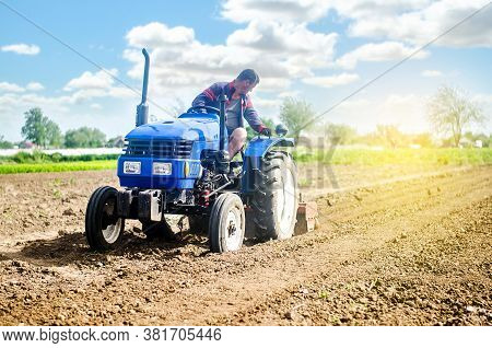 Farmer On A Tractor Loosens The Soil With Milling Equipment. Loosening Surface, Land Cultivation Use