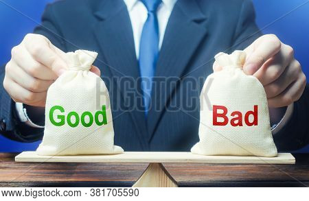 Businessman Holds Good And Bad Bags On Scales. Evaluating The Actions Of Other People, Weighing The