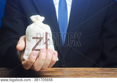 A Businessman Holds In His Hand A Polish Zloty Money Bag. Stimulating Economic Recovery. Investments