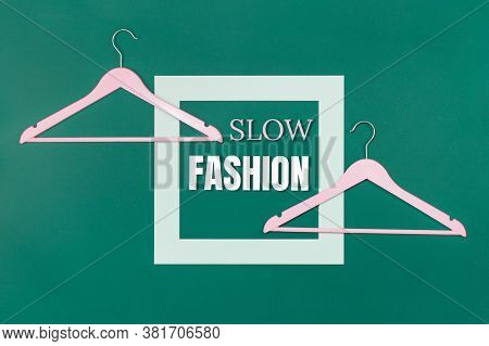 Slow Fashion Text And Two Empty Coat Hangers On Green Background. Sustainable Approach To Manufactur