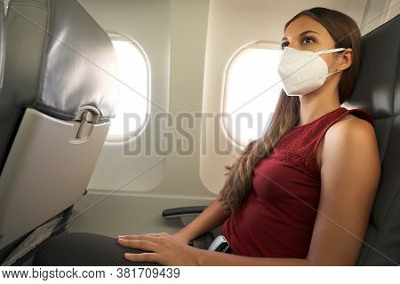 Fly Safe. Young Business Woman Wearing Kn95 Ffp2 Mask Is Traveling On Airplane. New Normal Travel Af