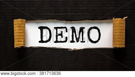 The Word 'demo' Appearing Behind Torn Black Paper. Business Concept.