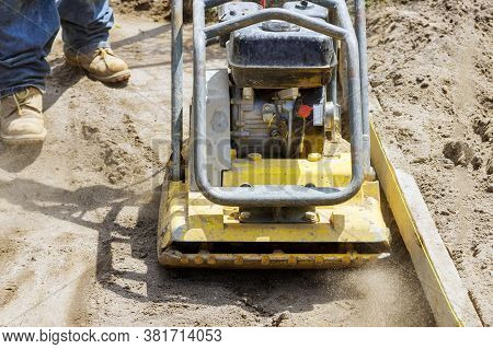 Vibratory Plate Compactor Worker Uses Compactor To Soil At Worksite Under Construction