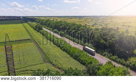 Aerial. Truck Driving By The Roadway Between Agricultural Fields.