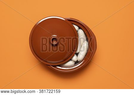 Boiled White Sausage In A Brown Pot, Isolated On Orange Background. Top View Of Bavarian Veal Sausag