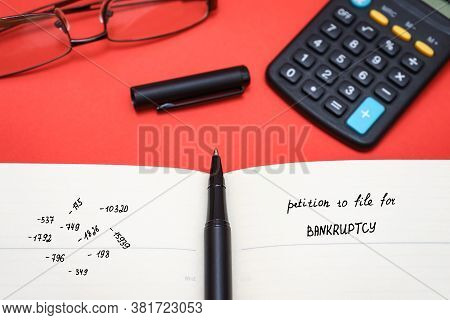 Petition To File For Bankruptcy With Glasses And Calculator. Calculation Of Expenses And Profits
