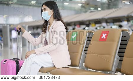 A Business Woman Is Wearing Protective Mask In International Airport, Travel Under Covid-19 Pandemic