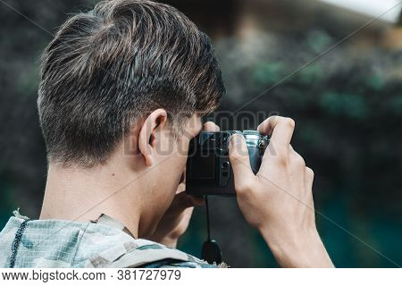 Digital Portable Camera In The Hands Of A Young Photojournalist