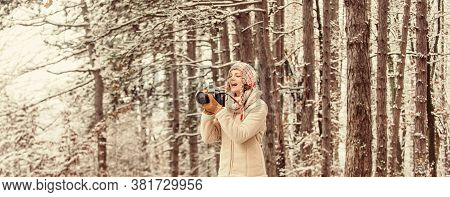 Stylish Hipster Traveler. Woman Holding Photo Camera. Taking Picture In Winter Forest. Photographer