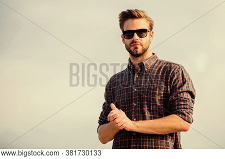 Man Eyewear Model Outdoors Blue Sky Background. Handsome Guy Wear Sunglasses. Hipster Man In Trendy