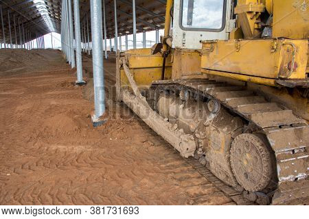 A Bulldozer Is Leveling The Ground In A Barn Under Construction. Construction Of An Agricultural Com