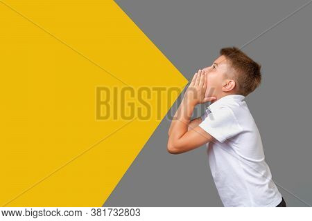 Boy Screams With Hands Folded As Megaphone Isolated On Gray-yellow Background