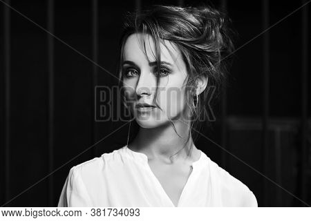 Sad young fashion woman in white shirt with bun updo hairstyle