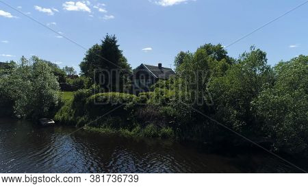 Summer Rural Landscape With Wooden House Near Lake. Shot. Sunny Day In A Russian Village With A Smal