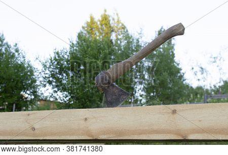 An Ax Stuck Into A Wooden Beam, Construction Of A Wooden House.