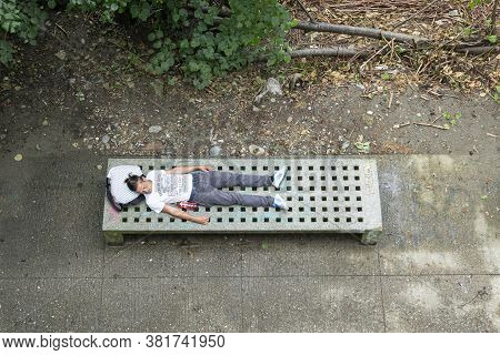 Graz, Austria. August 2020.  A Tired Young Man Rests Lying On A Bench On The Mur Riverfront
