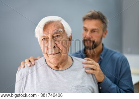 Old Senior Man With Dementia Getting Support And Care From Son