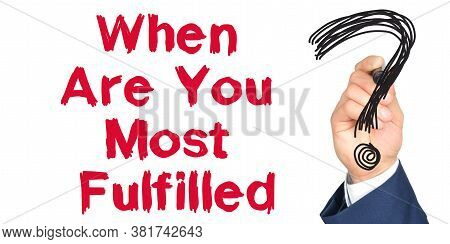 Hand With Marker Writing: When Are You Most Fulfilled. Hand Of A Businessman With A Marker.