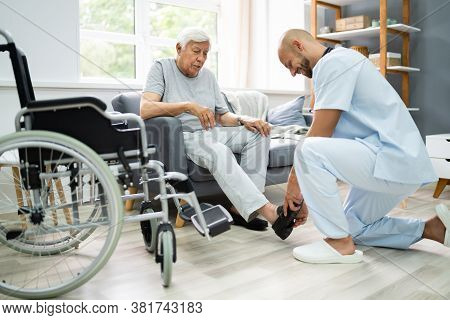 Old Senior Home Care. Nurse Helping Patient To Dress Shoes