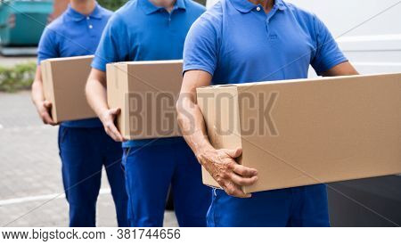 Truck Movers Loading Van Carrying Boxes And Moving House