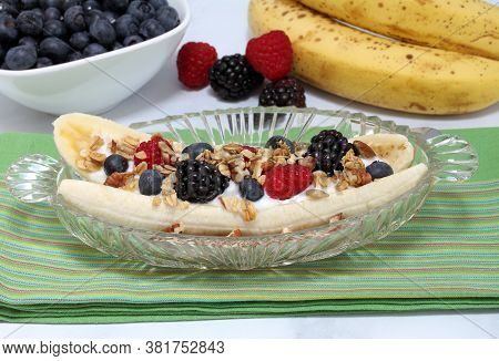 Blackberries, Blueberries, Raspberries, Granola, Nuts And A Banana Fruit Salad Styled Like A Banana