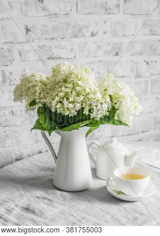 Bunch Of Hydrangeas In A Vintage Jug, Cup Of Green Tea, Teapot On The Table. Cozy Home Still Life