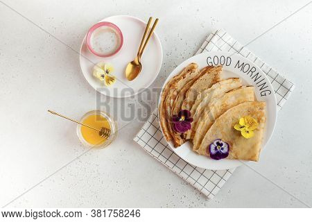 French Crepes, Pancakes Decorated With Flowers, A Mug Of Cappuccino And Honey. Concept Of Breakfast,