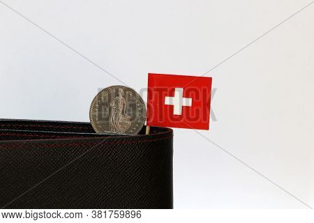 One Coin Of One Swiss Franc And Mini Switzerland Flag Stick On The Black Wallet With White Backgroun