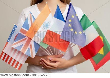 World Peace. Global Unity. Woman Holding International Flags Isolated On Light Background. Political