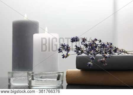 Wax Candles In Glass Holders Near Books And Lavender Flowers On Table Against Light Background