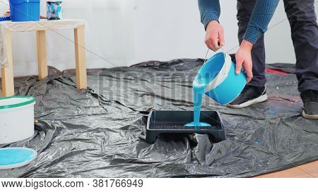 Man Pouring Blue Paint From Can For Home Renovation. Apartment Redecoration And Home Construction Wh