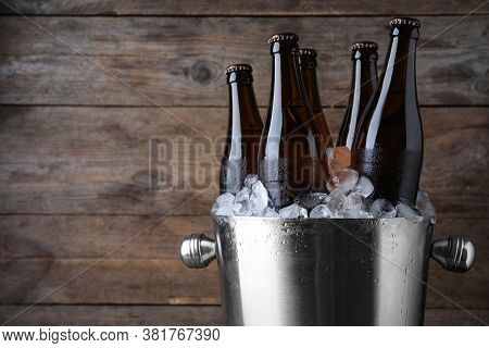 Metal Bucket With Beer And Ice Cubes On Wooden Background, Closeup. Space For Text