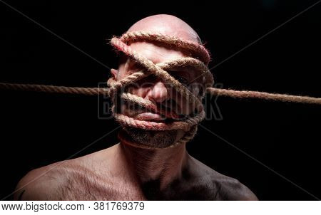 Portrait Of Binded Bald Adult Man With Rope On Face