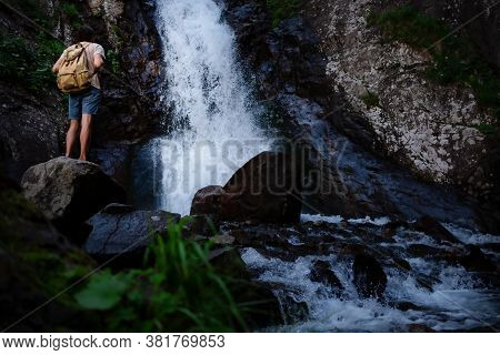 Hiker Waalkinh With Backpack Looking At Waterfall In Park In Beautiful Nature Landscape.
