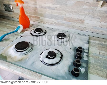 Gas Stove Is Covered With Cleaning Foam. Cleaning A Modern Gas Stove.