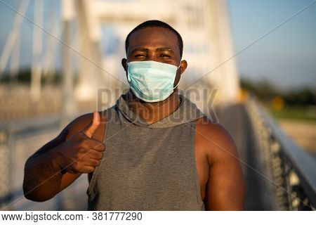 Portrait Of Young African-american Man With Protective Mask On His Face. Corona Virus Pandemic Respo